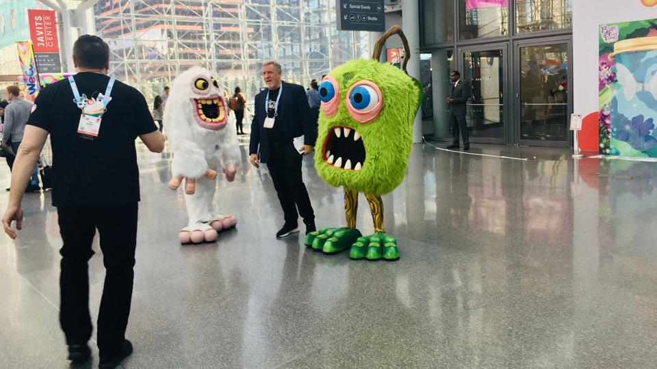 A picture of a scene at the New York Toy Fair on Sunday, February 23, 2020, with two costumed characters posing with a show attendee.