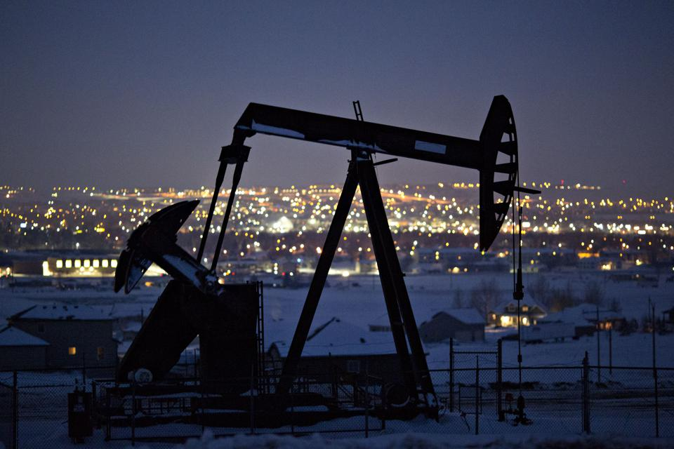 A pumpjack operates above an oil well at night in the Bakken Formation