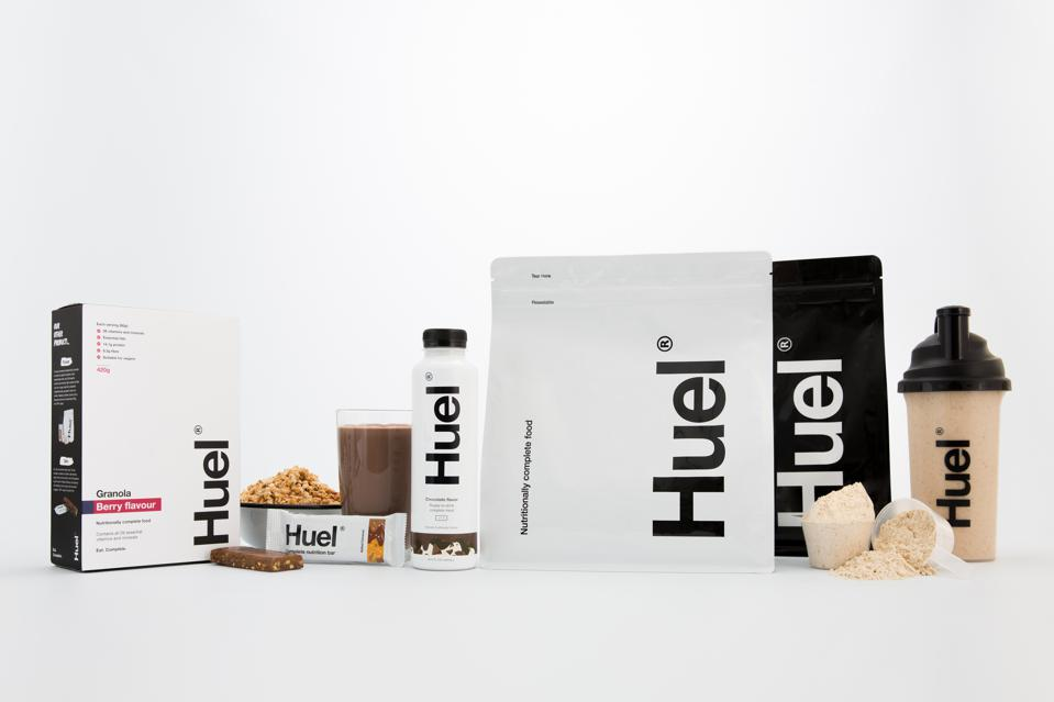 An assortment of Huel's product line including its ready-to-drink product, bar, shaker and powder.