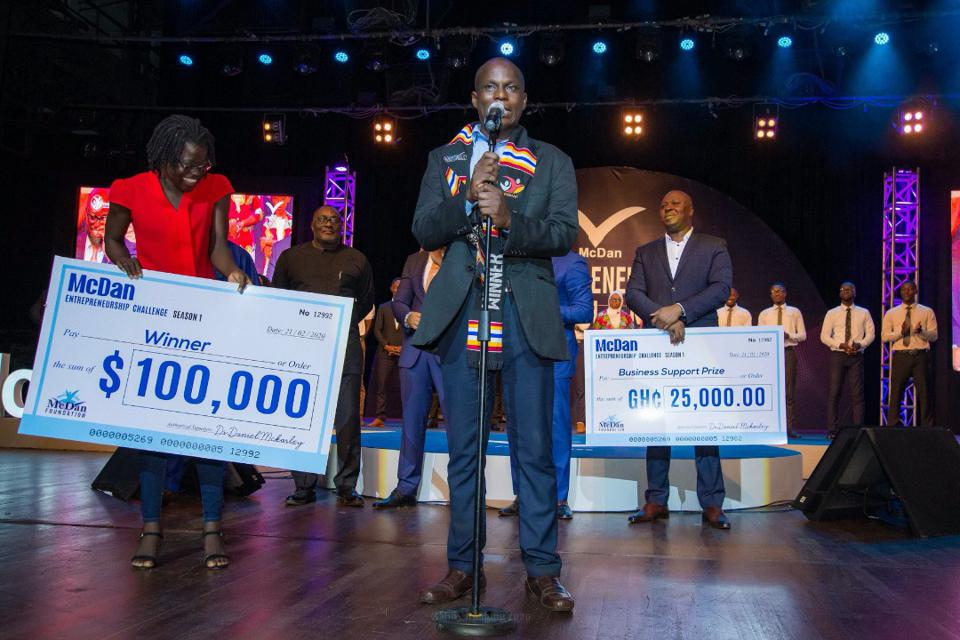 African men and women on a stage holding big checks