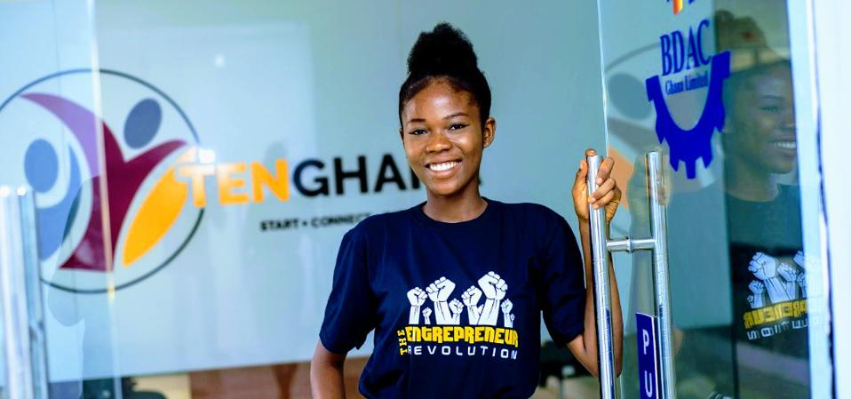 A smiling young African woman looking out an open door.