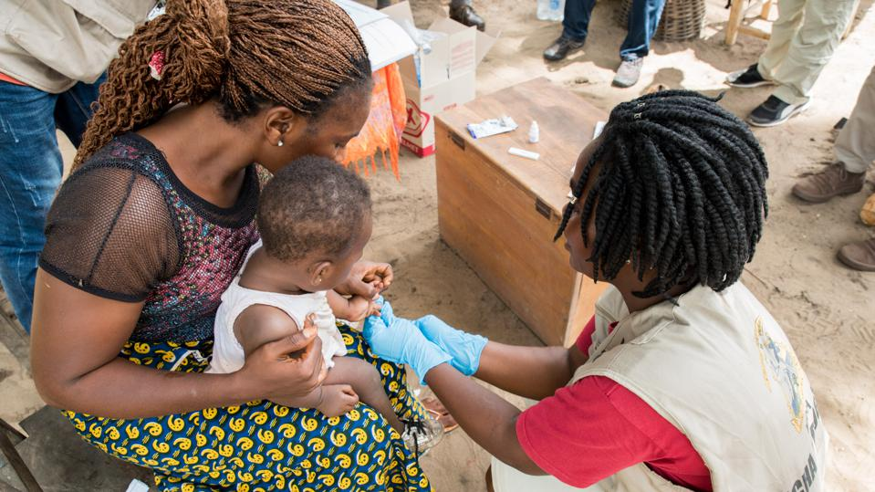 A community health worker in Liberia conducts a diagnostic test for malaria on a young patient