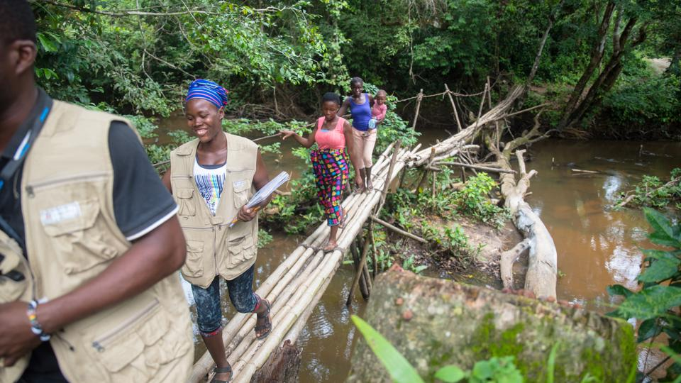A patient and his mother travel alongside community health workers to reach a health clinic in rural Liberia