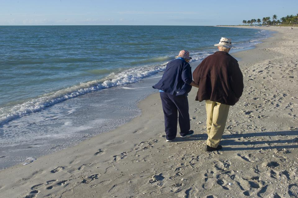 Elderly couple walking the beach in Florida.