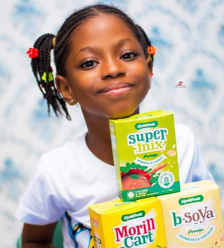 A fresh-faced young African girl posing with food products