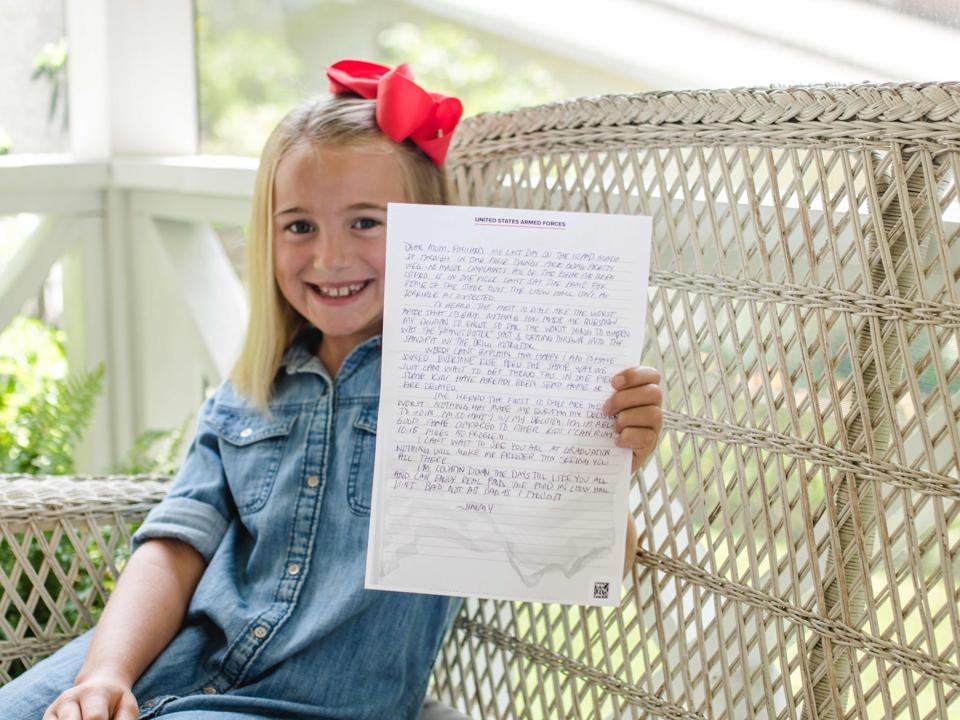 A smiling little girls holds up a letter.