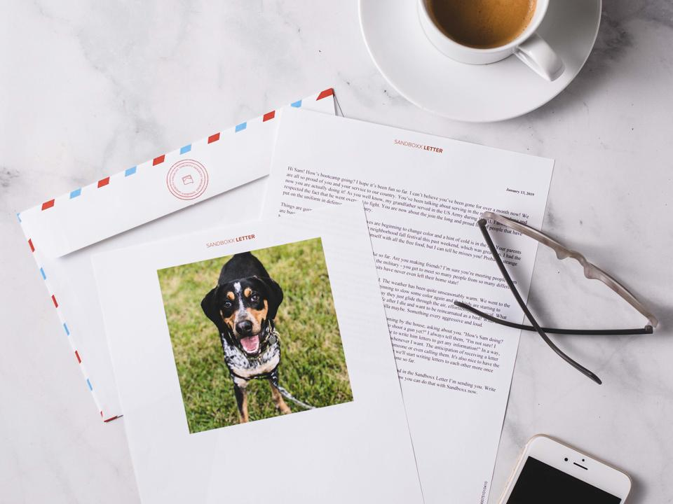 A letter with a photo of a dog sits on a table with reading glasses and a smartphone.