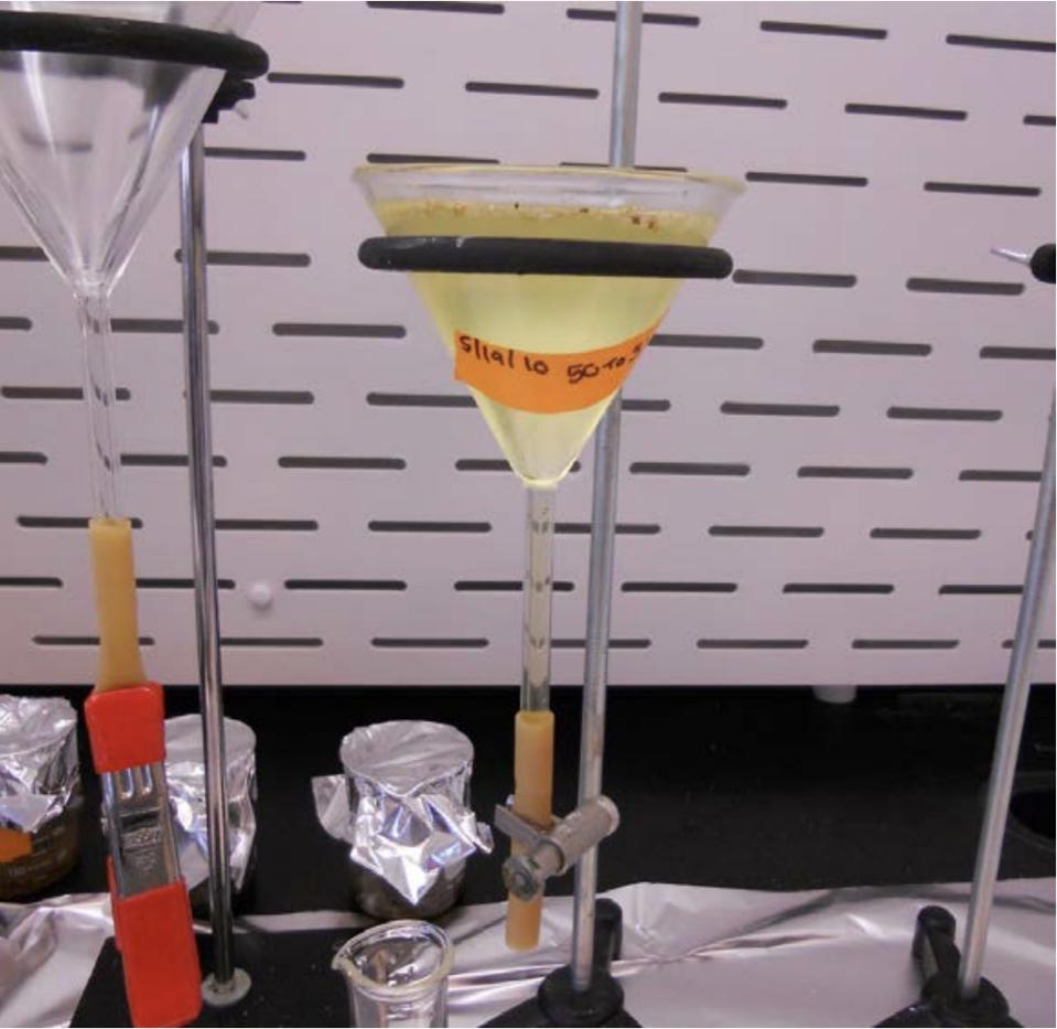 A funnel with a yellow peroxide solution for separating microplastics out of water.