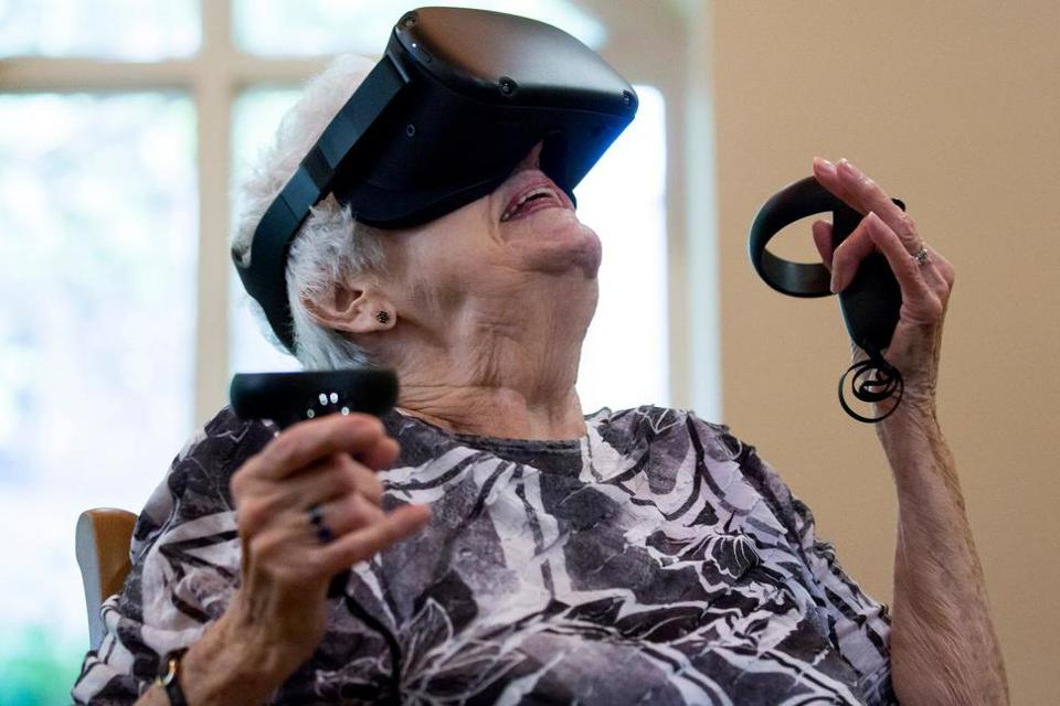 This photo shows Joy Kay, resident at The Fountains at La Cholla, using a virtual reality device to ride a roller cosater similar to the one she grew up with during athe virtual reality program, ″EngageVR″.