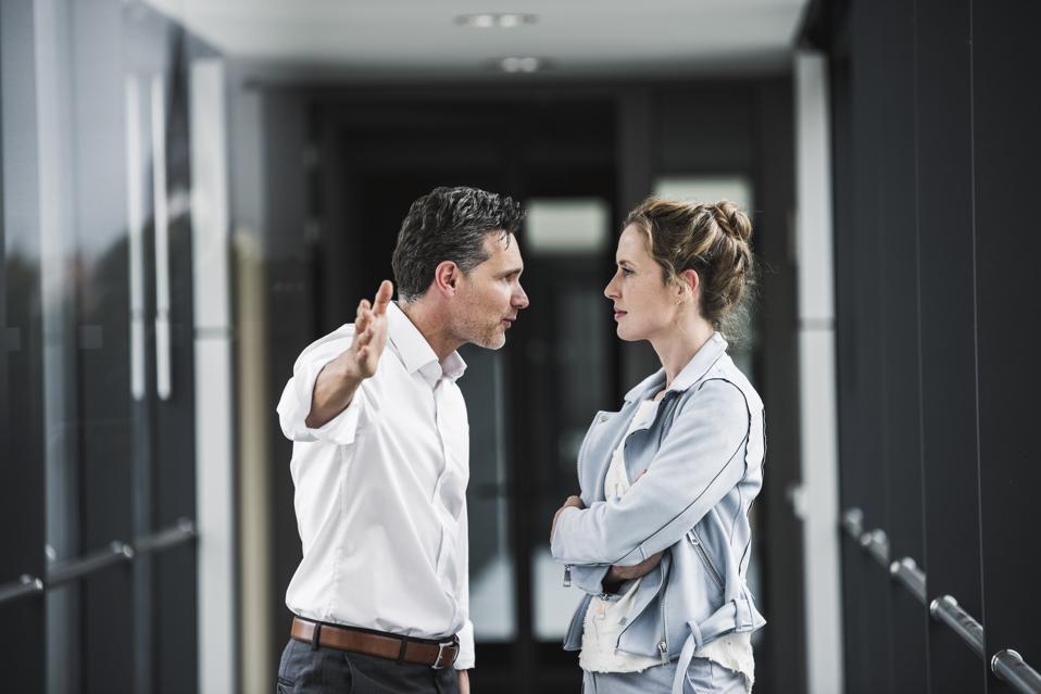 Businesswoman and businessman arguing in office passageway