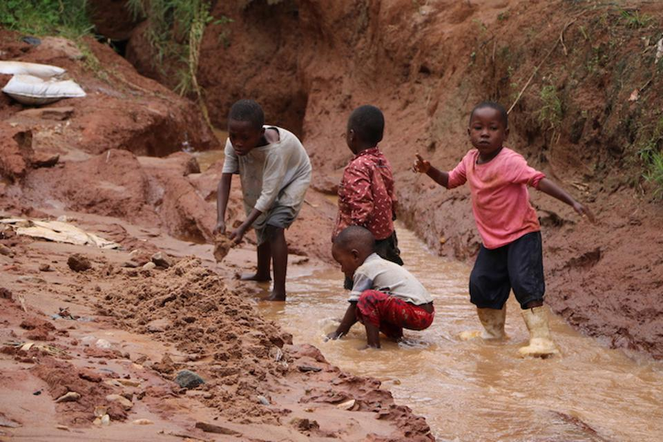 On January 29, 2020, children play in the muddy remains of a road washed away by severe flooding in Bujumbura, Burundi.