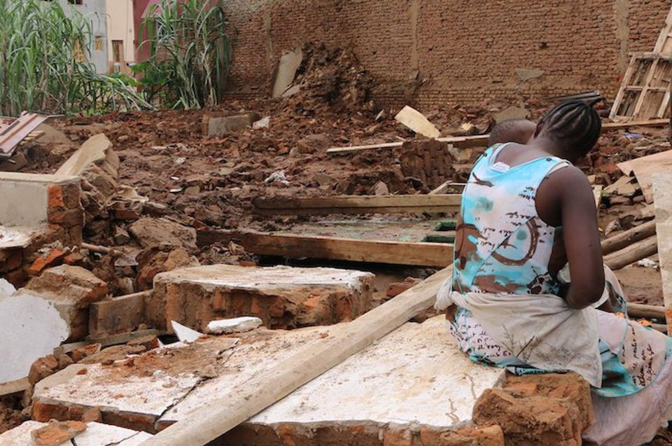 A young mother sits beside the ruins of her home, which collapsed in the night in the Kanyosha neighborhood of Bujumbura, Burundi.