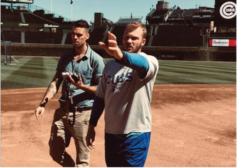 Ian Happ leading artist Pat Vale around Wrigley Field.