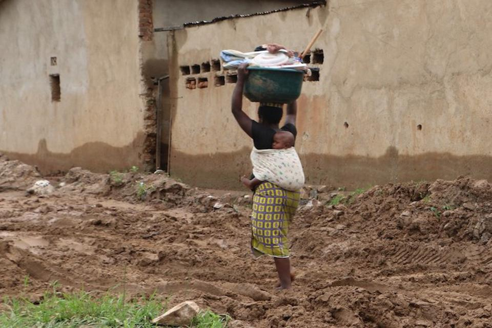 In Bujumbura, Burundi, a woman with a baby on her back carries a basin filled with cooking materials she was able to salvage from the remnants of her home.