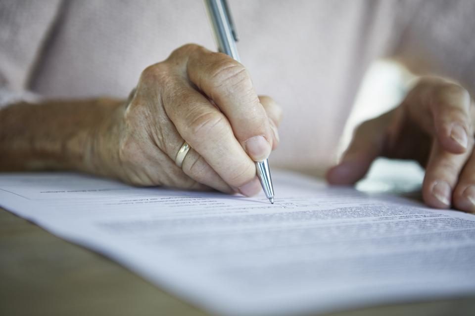 Senior woman's hand signing a document, close-up