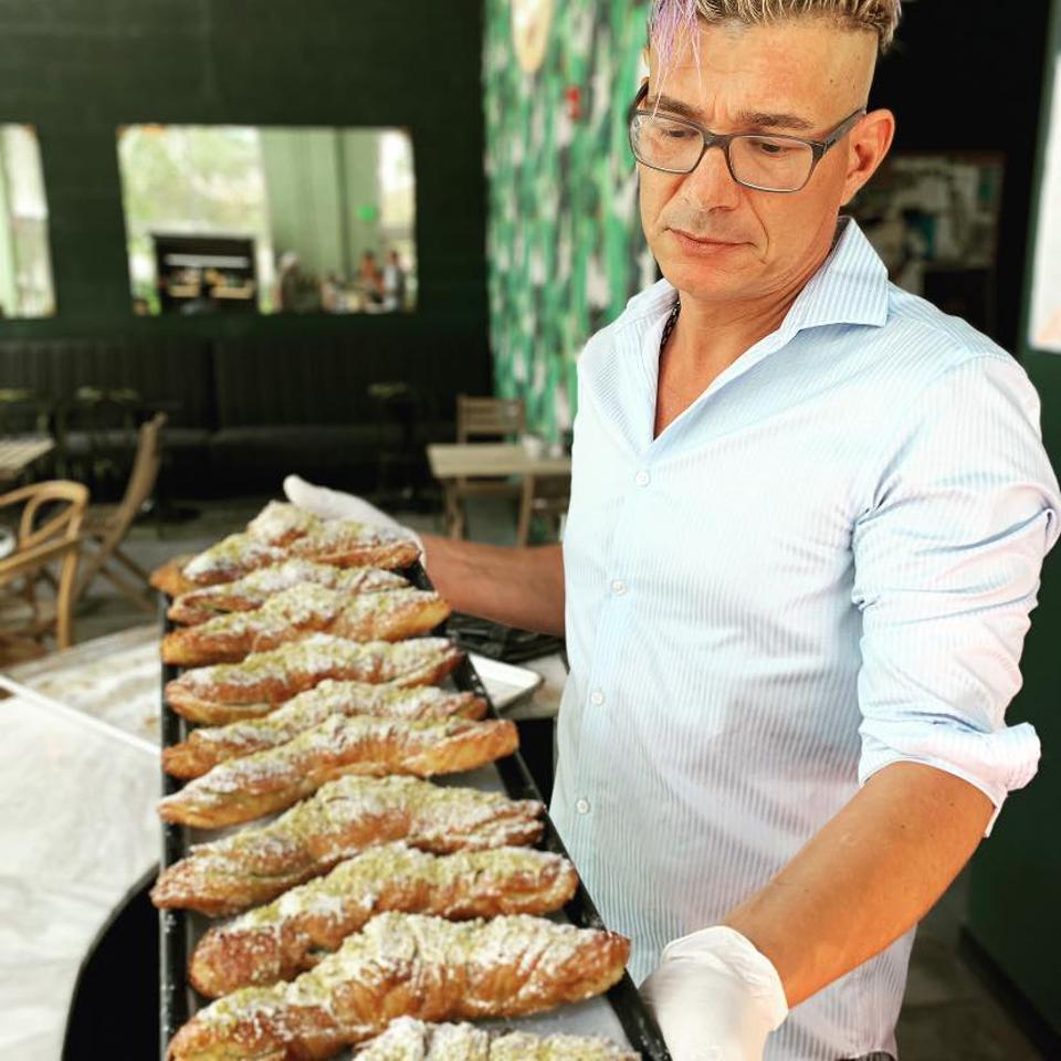 Loic Bakery owner Loic Autret with a pan of croissants.