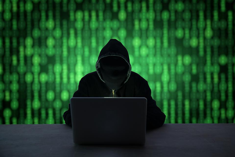 Hacker With Obscured Face Using Laptop At Desk