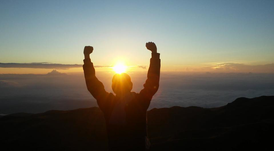 Man facing the sunset with arms upraised in victory