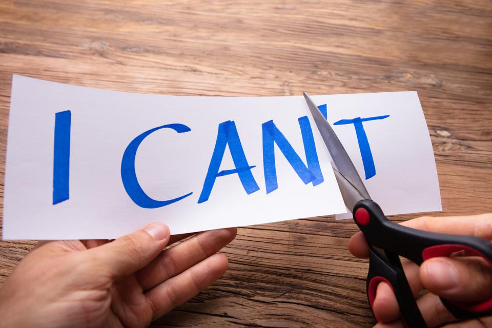 A person's hand holding a piece of paper that says ″I CAN'T″and cutting off the ″T″ with a pair of scissors.