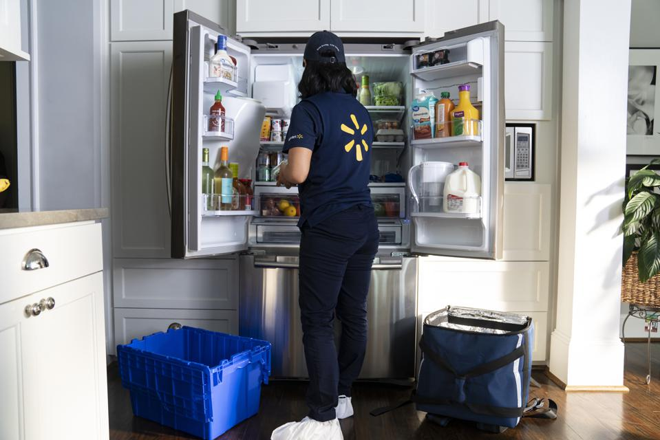 Associate stocking a fridge with Wal-Mart InHome Delivery