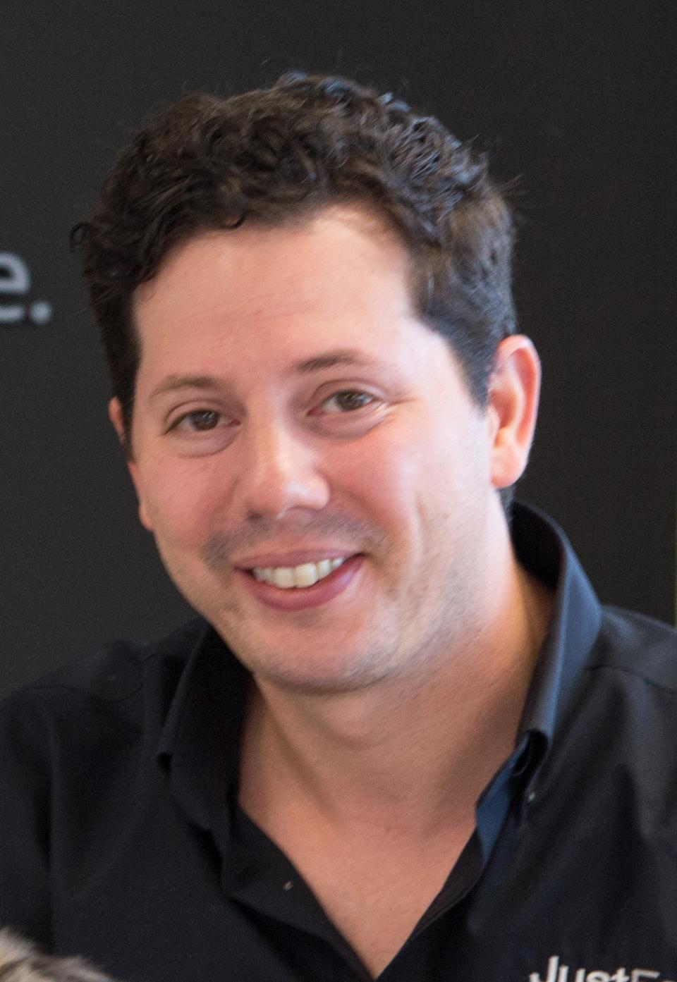young smiling man in open collar black shirt
