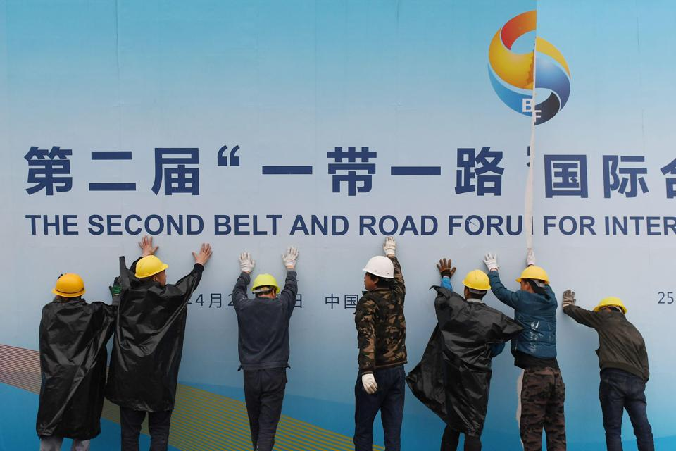 Workers take down a Belt and Road Forum panel.