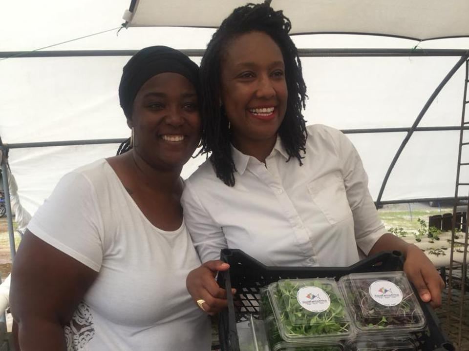 Two African-American women pose with a crate of produce in a greenhouse.