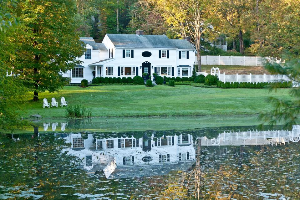 A white house with a pond.