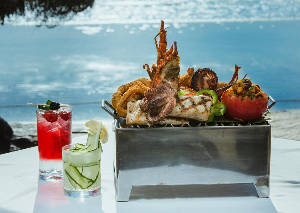 seafood on a grill with cocktails at the beach