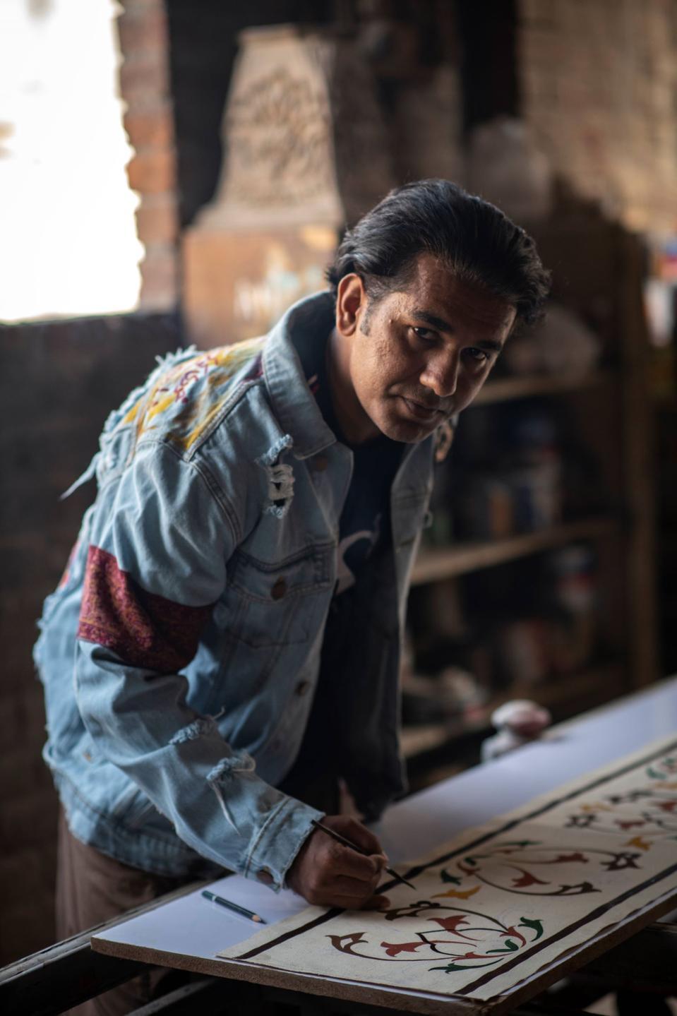 A Rastah artisan models Rastah's denim jacket.