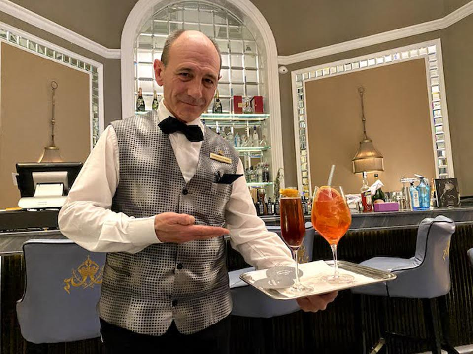 Alex serving a Kir Royale and an Aperol Spritz