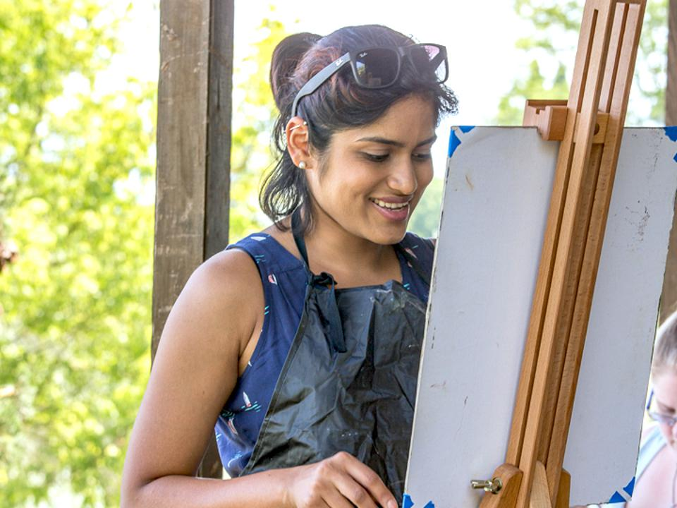 Doongarwal stands in an apron at a canvas, painting.