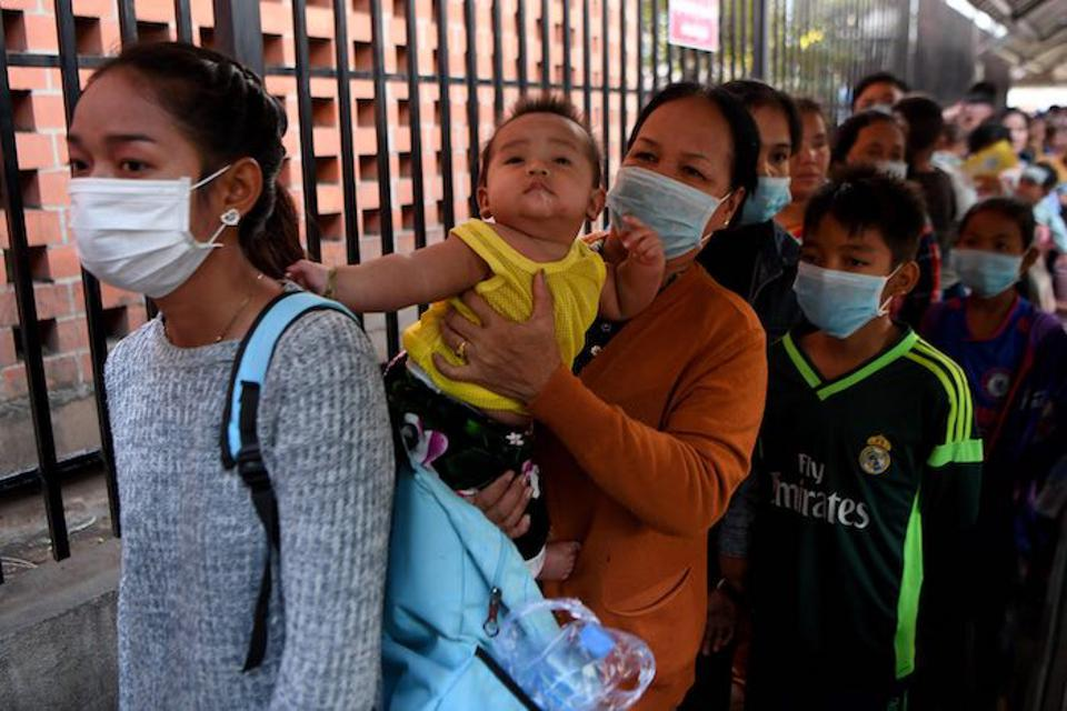 Despite popular belief, masks should only be worn by people who have coronavirus or those who are treating the sick. Above, women and children line up outside a hospital in Phnom Penh, Cambodia.