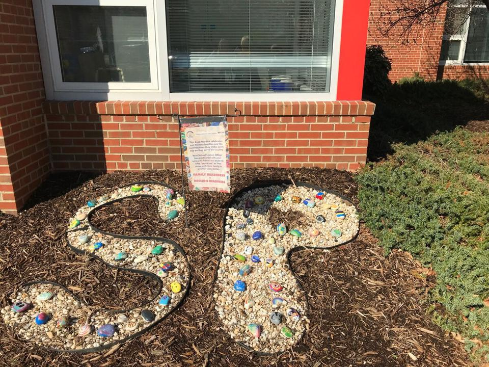 A school rock garden features special rocks painted and placed by military-connected students who have moved away from the area.