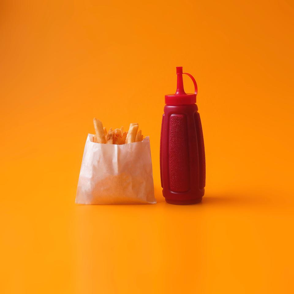 A package of delicious French fries alongside a dispenser of ketchup