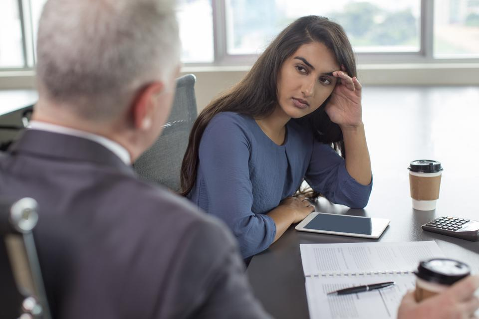 Business leader instructing serious Indian female assistant