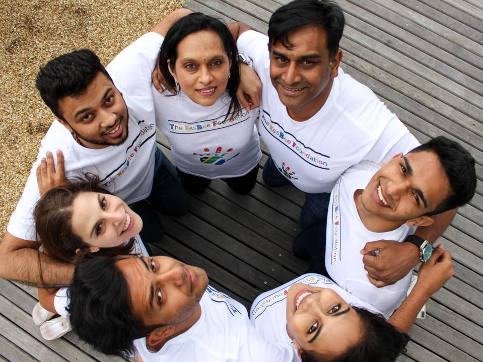 A group of 7 volunteers stand in a circle, looking up at the camera.