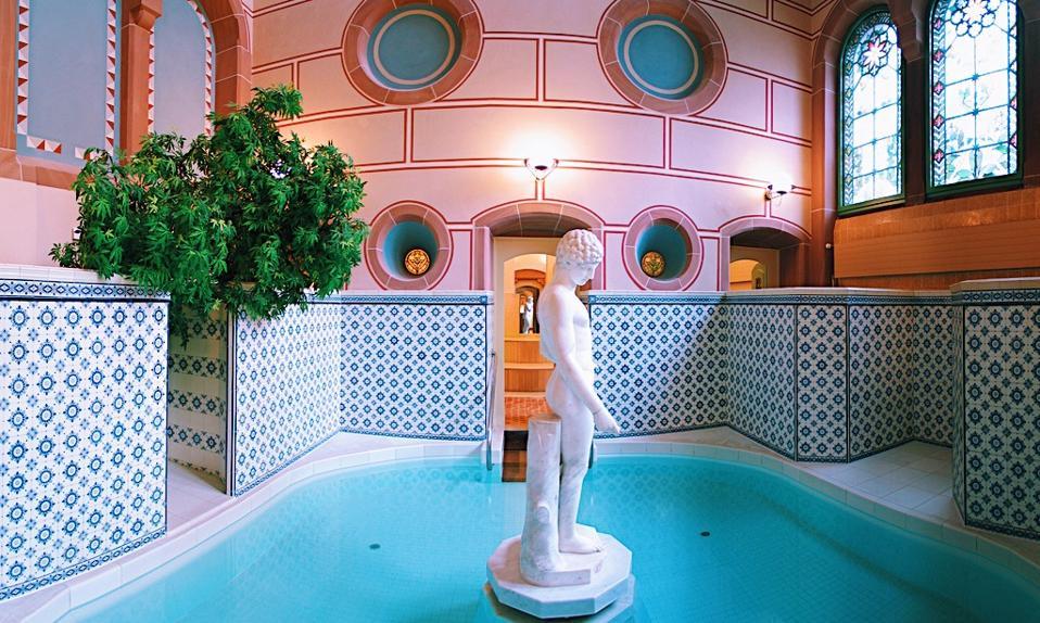 Une statue dans une piscine thermale entourée de tuiles à la station thermale du Palais à Bad Wildbad.