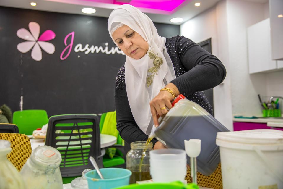 Falak, an employee of Syrian Jasmine Workshop, makes soap.