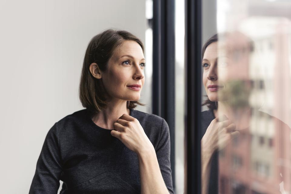 Thoughtful businesswoman looking through window