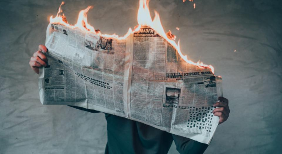 Person reading burning newspaper