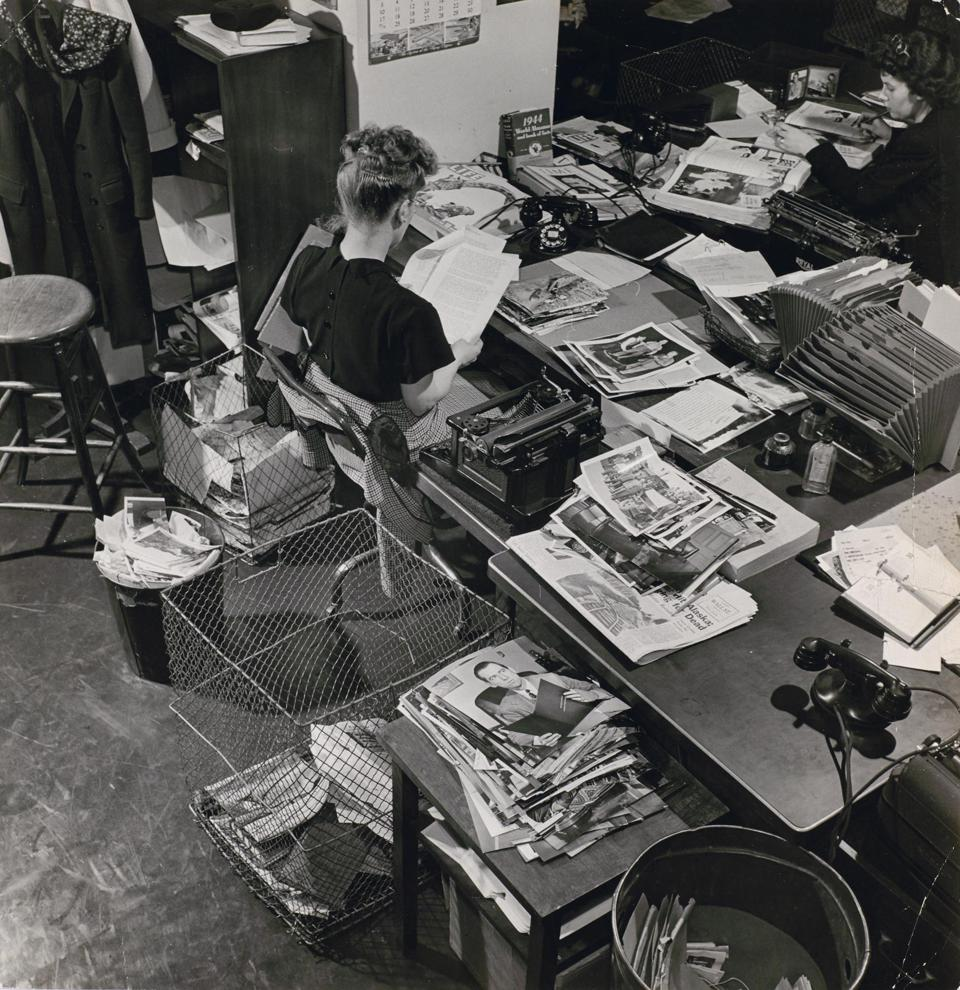 Unknown photographer, Life photo editor Natalie Kosek reviews photographs, 1946. Gelatin silver print. LIFE Picture Collection.