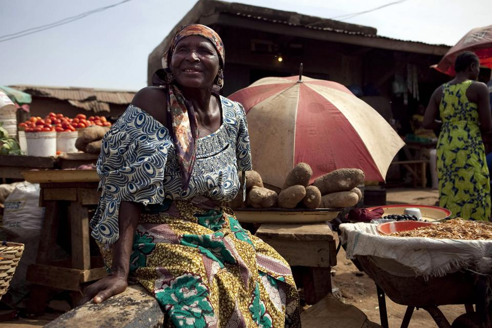 A woman sells food items at a local market in Nigeria.
