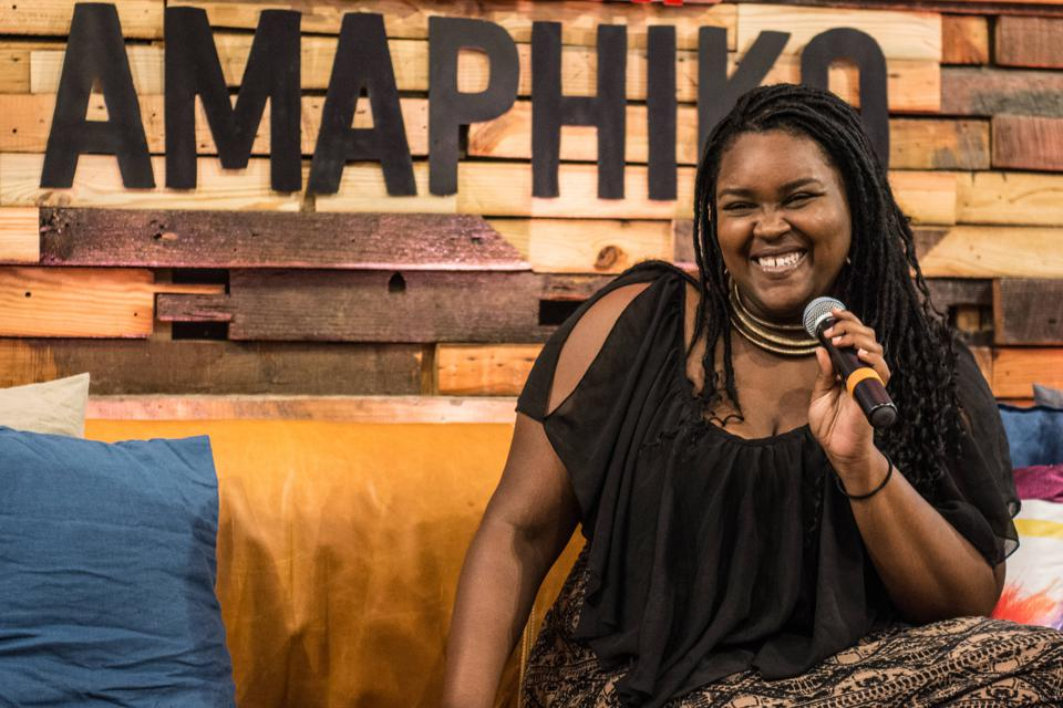 A woman holding a microphone and smiling