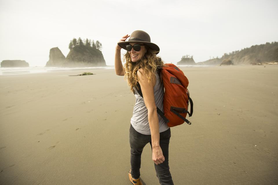 A woman hiking along a remote beach. travel empowers women