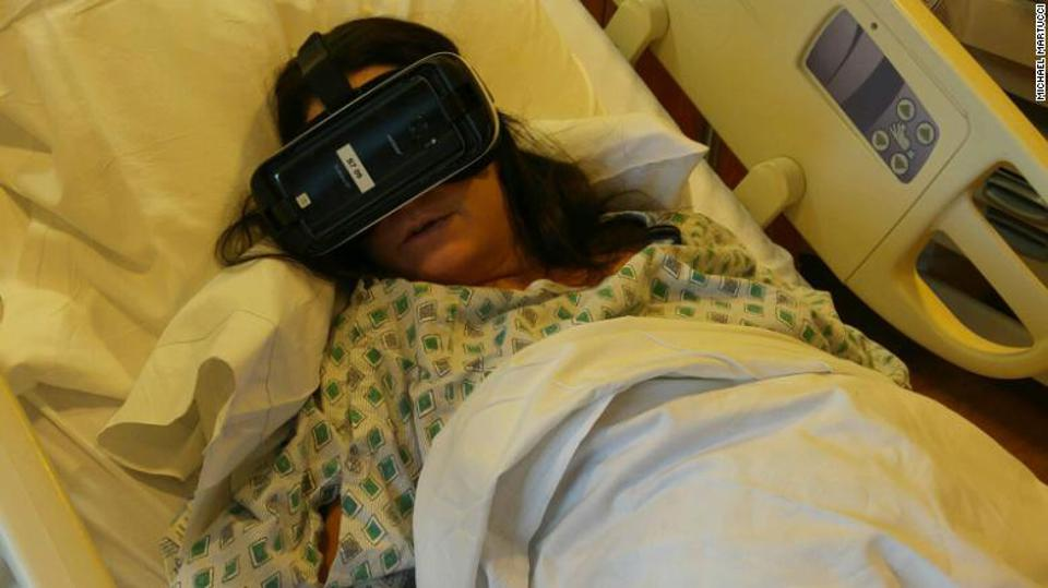 Woman wearing VR headset during labour, in a hospital bed