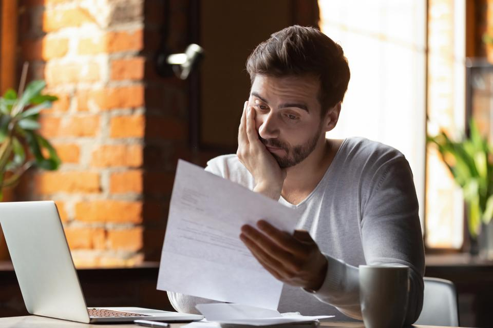 Confused frustrated man reading letter in cafe.