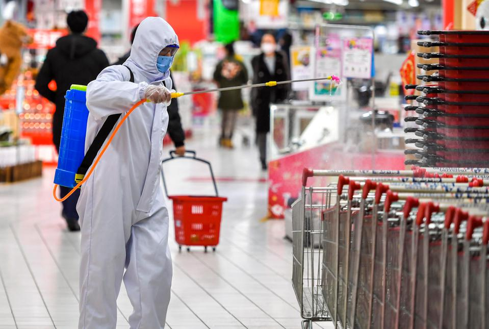 An employee wearing protective suit disinfects trolleys.