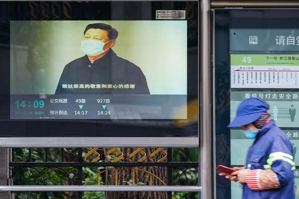 A pedestrian walks by a screen showing a video of Chinese president Xi Jinping.