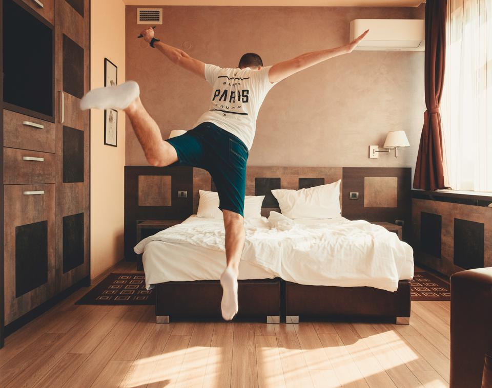 Man jumps onto his bed